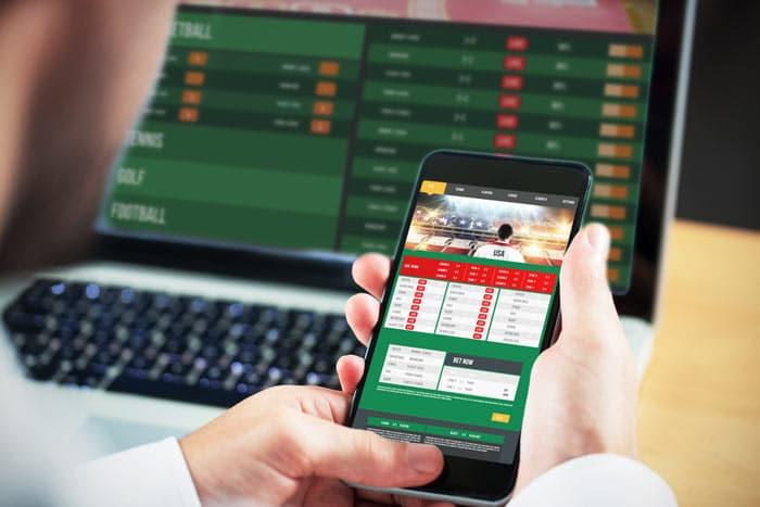 Mann nutzt die Dienste von Sportwetten-Anbietern auf dem Laptop und dem Smartphone